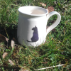 wheel-thrown mug with slip decorated cat